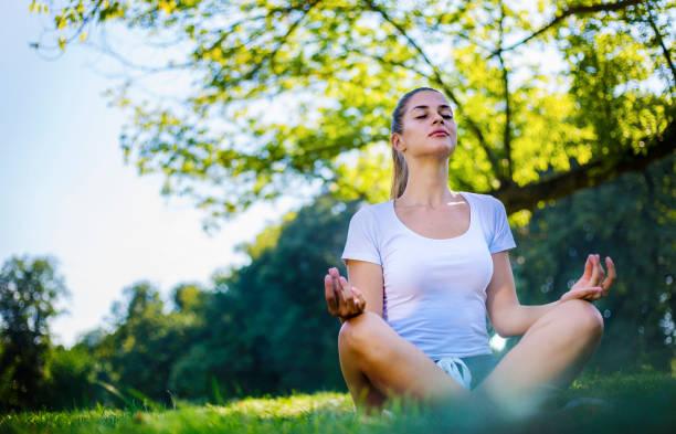 Beautiful woman meditating in city park stock photo
