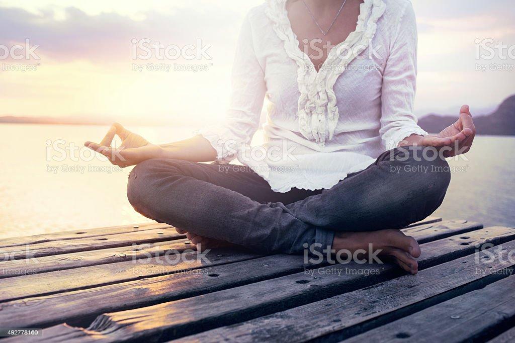 beautiful woman meditating on a boardwalk at sunset stock photo