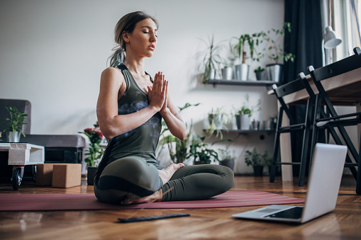 One beautiful young woman sitting in lotus pose on exercise mat in her living room and meditating.