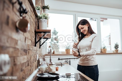 istock Beautiful woman mixing ingredients in a glass bowl in modern rustic kitchen. 1153781532