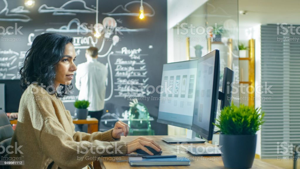 Beautiful Woman Mobile Game Application Developer Works on a Personal Computer, Designing Wireframe. She and Her Coworkers Work in the Creative Indie Studio. royalty-free stock photo