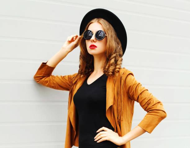 schöne frau modell trägt einen schwarzen hut, sonnenbrille und jacke suchen im profil über urbane grauen hintergrund - bedruckte leggings stock-fotos und bilder
