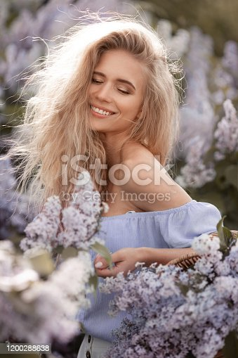 1054970060 istock photo Beautiful woman model with long blonde hair collects flowers in straw basket 1200288638