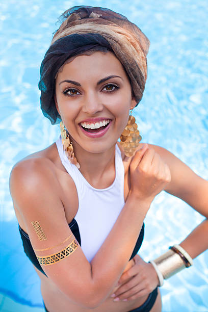 beautiful woman near the pool wearing colored turban - armband water stock-fotos und bilder