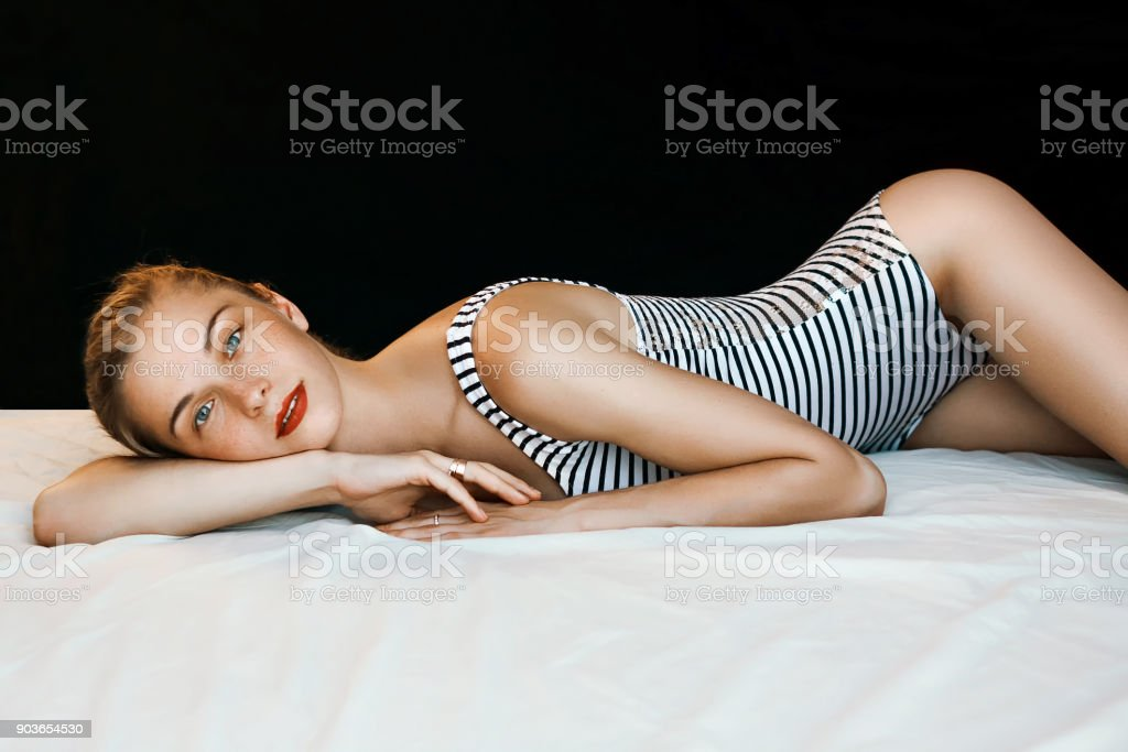 Beautiful woman nice figure blue eyes laying on the bad in sexy strips bodysuit stock photo