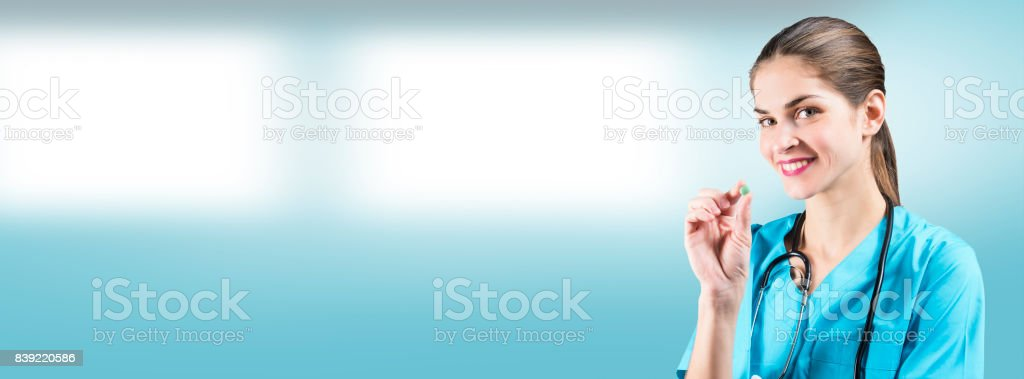 beautiful woman nurse or doctor is holding a pill with copy space for an advertising cover picture stock photo