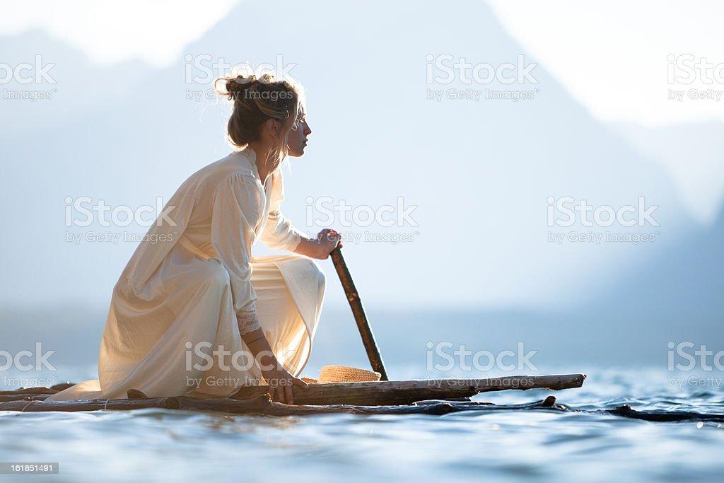 Beautiful woman on a wooden raft royalty-free stock photo
