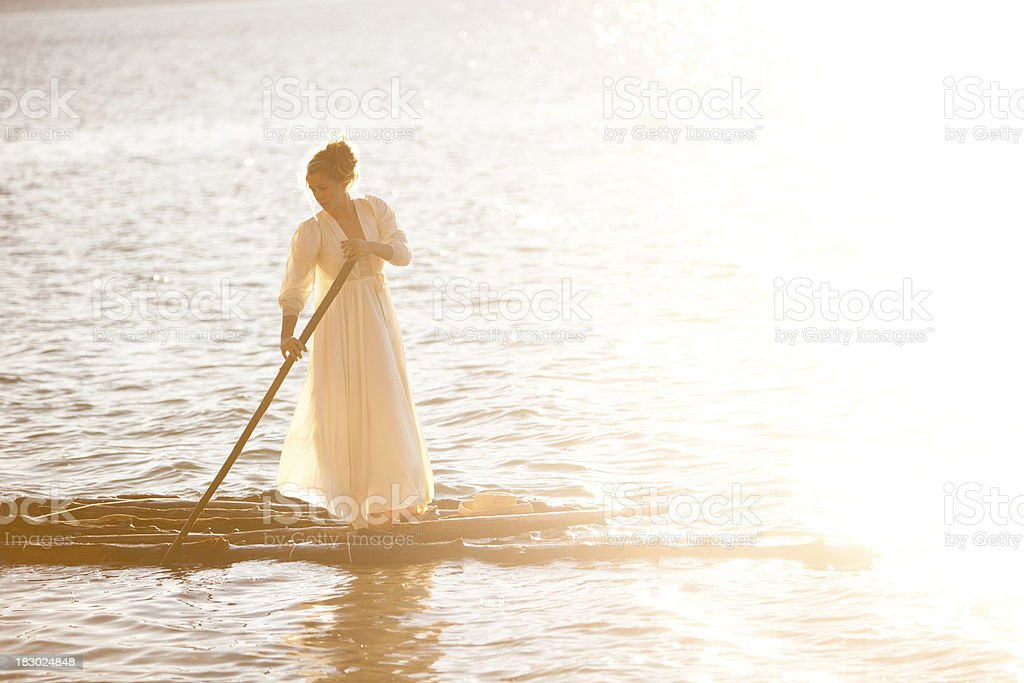 Beautiful woman on a wooden raft royalty-free stock photo
