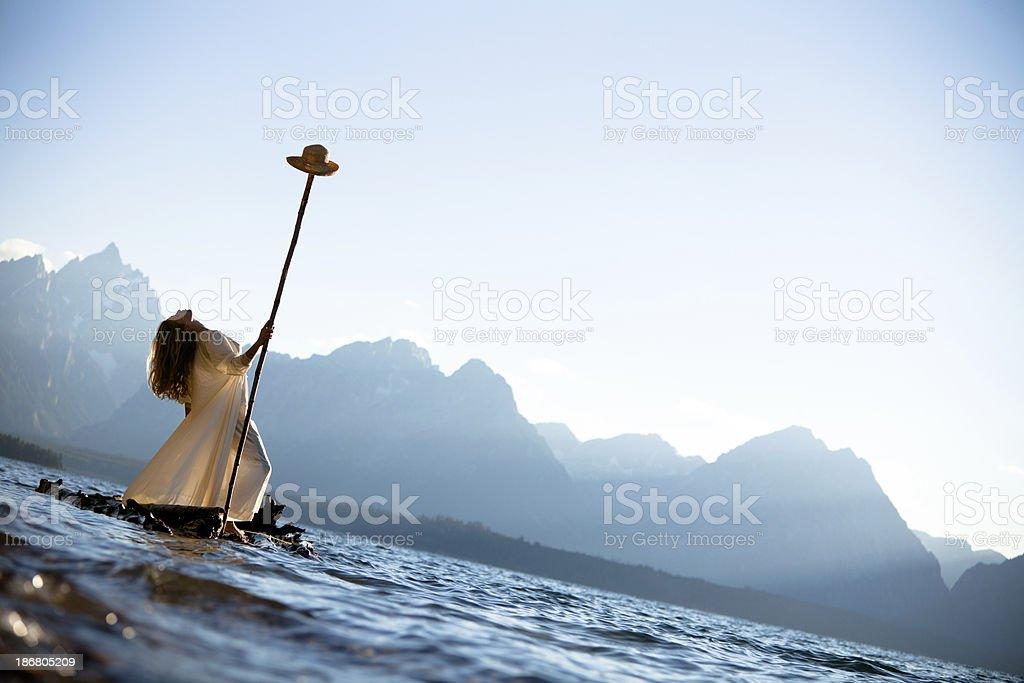 Beautiful woman on a wooden raft stock photo
