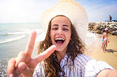 Beautiful young woman on beach wearing striped blue-and-white shirt and hat, laughing, taking selfie, showing peace sign. Enjoying time at seaside.