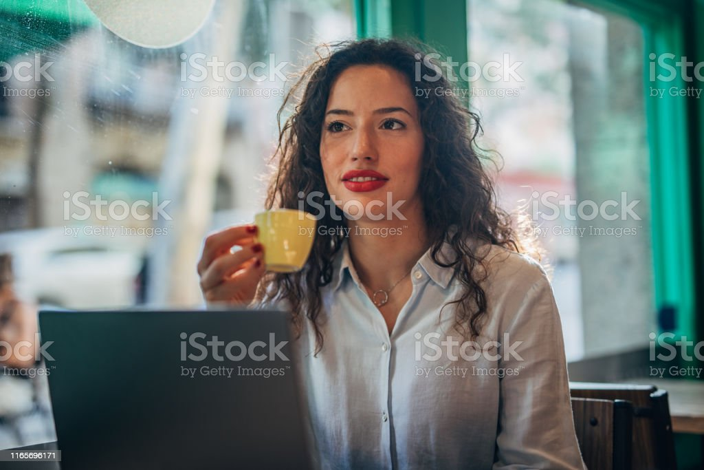 One woman, beautiful young lady on coffee break in cafe, using laptop.
