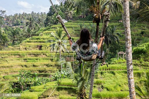 Beautiful woman on high swing above rice fields in Bali on sunny day