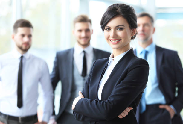 beautiful woman on the background of business people - woman suit stock photos and pictures