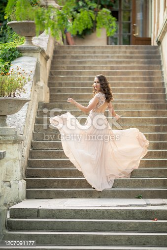 istock Beautiful woman on the background of steps in a beautiful wedding dress in full growth 1207091177