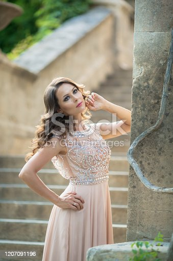506798692 istock photo Beautiful woman on the background of steps in a beautiful wedding dress in full growth 1207091196