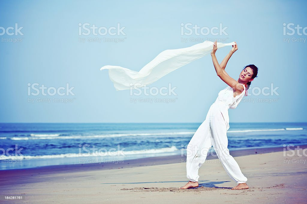 Beautiful woman on the beach Beautiful woman wearing in white standing on the tropical beach and holding white shawl in her hands with wind blowing. 25-29 Years Stock Photo