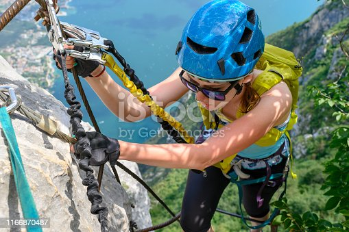 Beautiful woman on via ferrata trail, above Garda lake