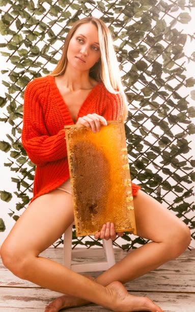 schöne frau offene beine und wabenhonig - bienenstock stock-fotos und bilder