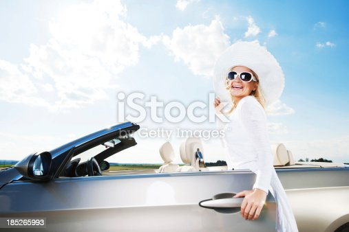 Glamorous female is entering her cabriolet car.