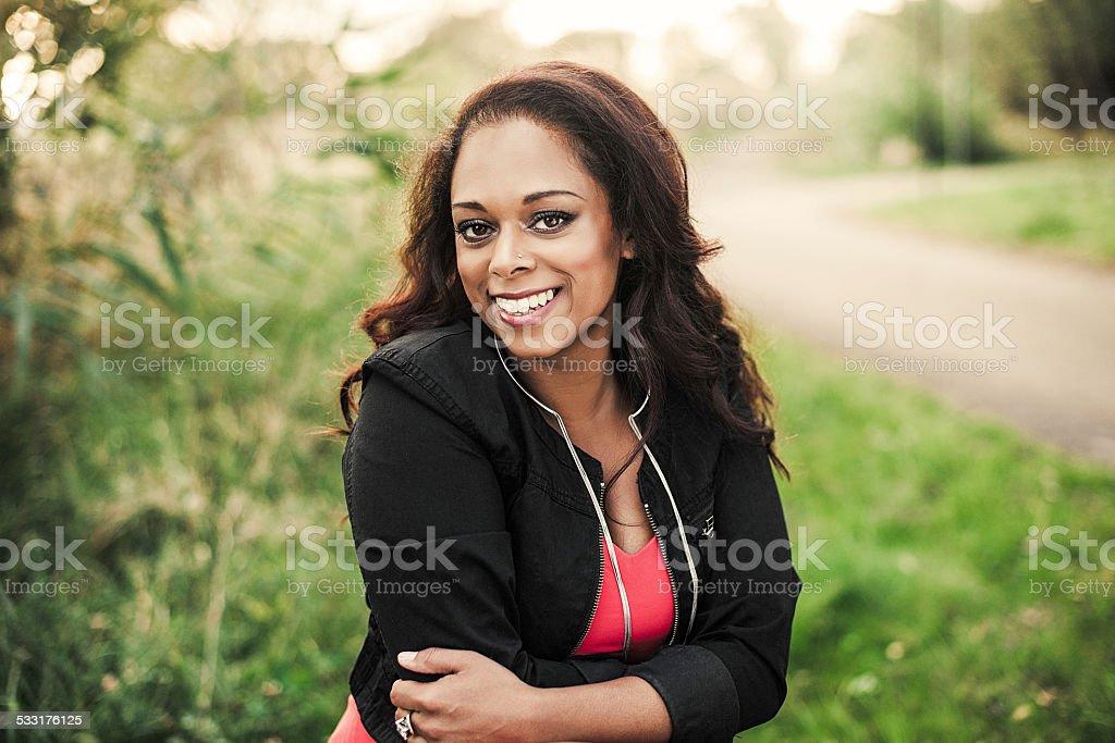Beautiful woman outdoors in green foliage stock photo