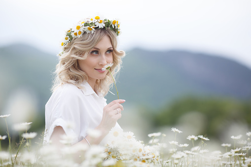 Beautiful woman outdoors with a bouquet of white daisies on a blooming mountain meadow