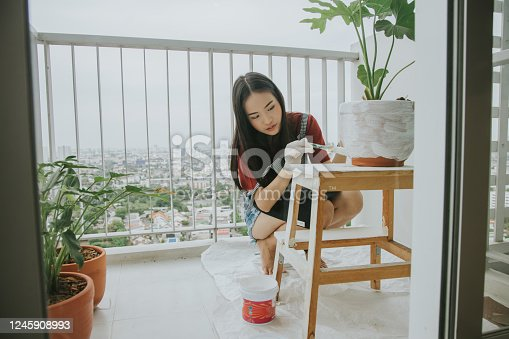 Home DIY with Thai woman painting her tree pot at her apartment in the city, Bangkok Thailand