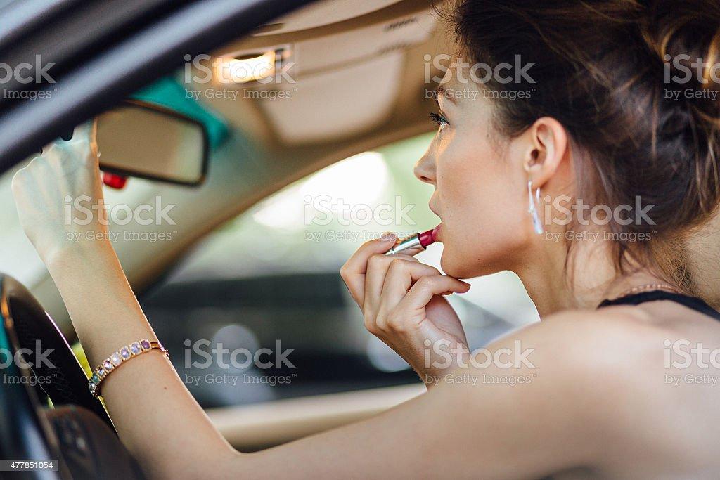 Mulher bonita tintas seus lábios - foto de acervo