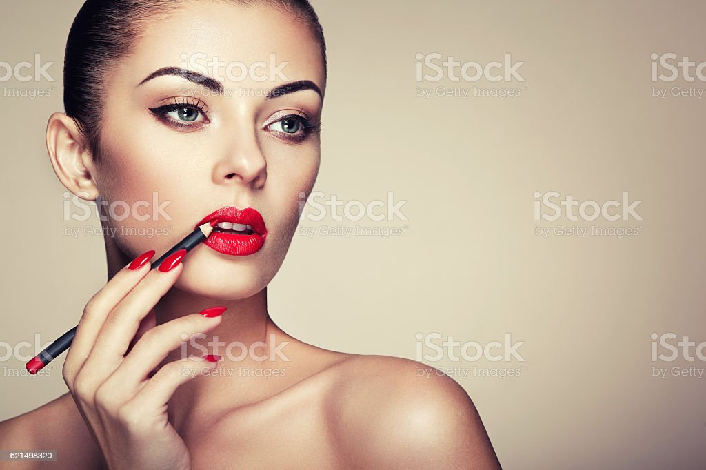 Beautiful woman paints lips with lipstick photo libre de droits