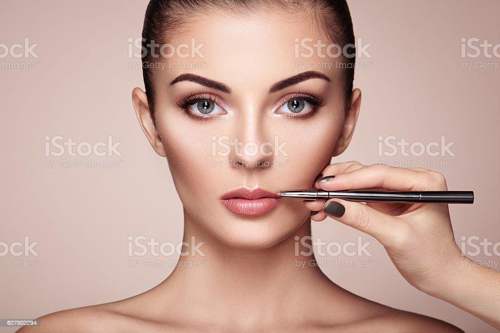 Beautiful woman paints lips with lipstick stock photo