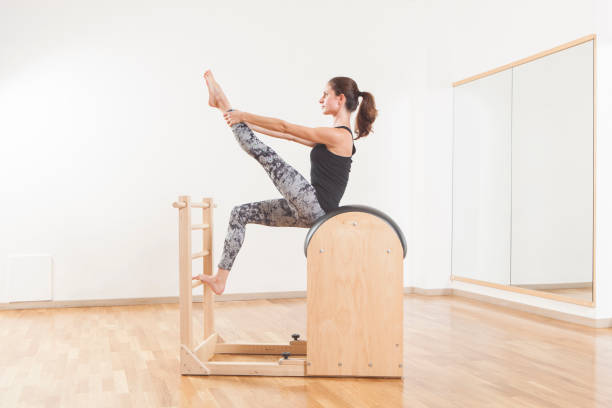 Beautiful woman performing pilates exercise, training on barrel equipment stock photo