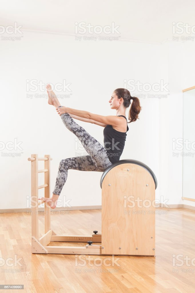 Beautiful woman performing pilates exercise, training on barrel equipment stock photo