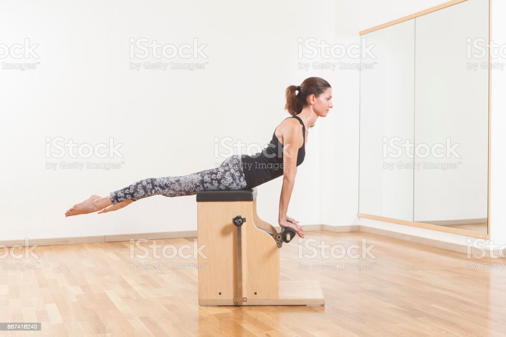Beautiful woman performing pilates exercise, training on chair equipment stock photo