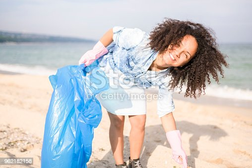 962184460 istock photo Beautiful woman picking up garbage during local clean up 962182158
