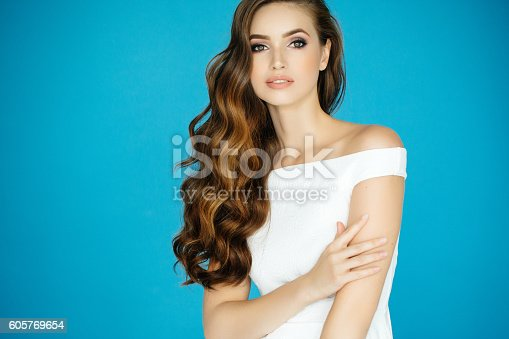 Studio shot of young beautiful woman on dark background. Professional make-up and hairstyle.