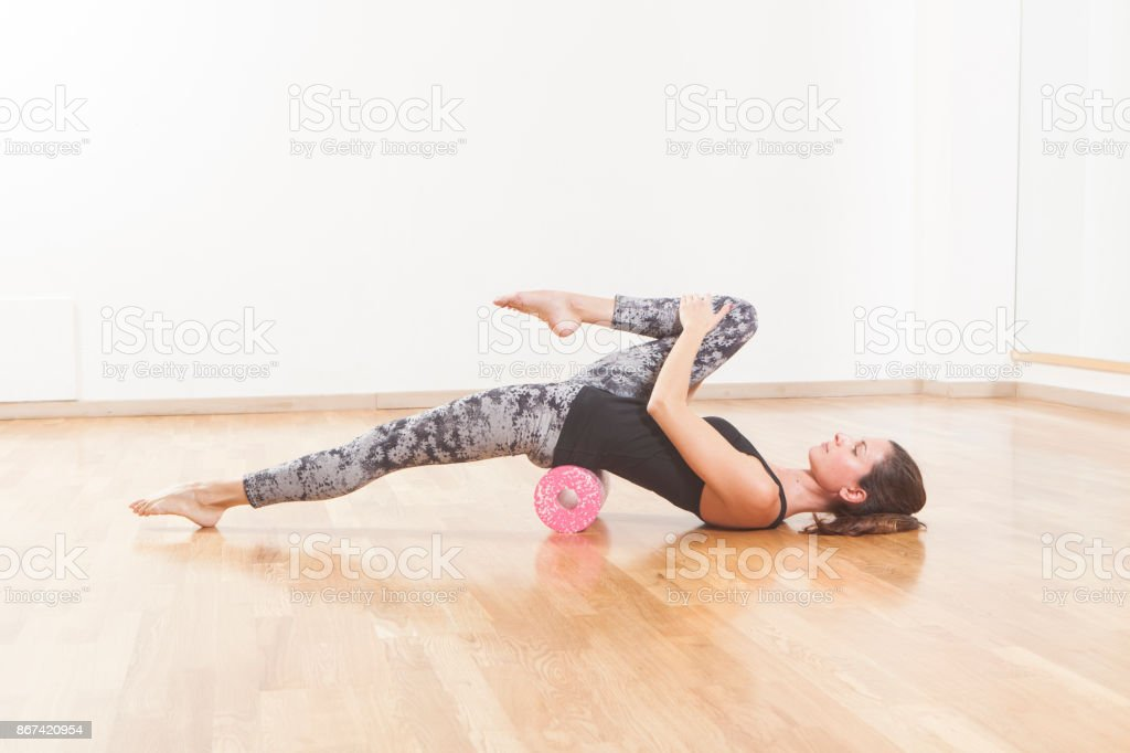 Beautiful woman pilates instructor stretching and warming up using foam roller stock photo
