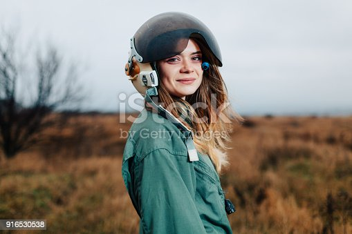 istock beautiful woman pilot of plane standing in the sunset field 916530538