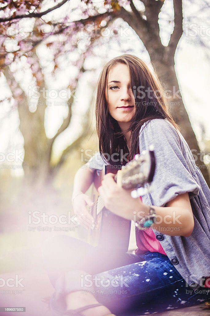 Beautiful woman playing guitar in blooming nature royalty-free stock photo
