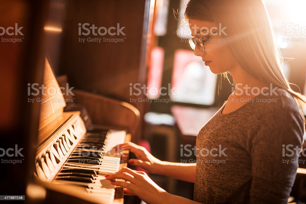 Beautiful woman playing old-fashioned piano. stock photo