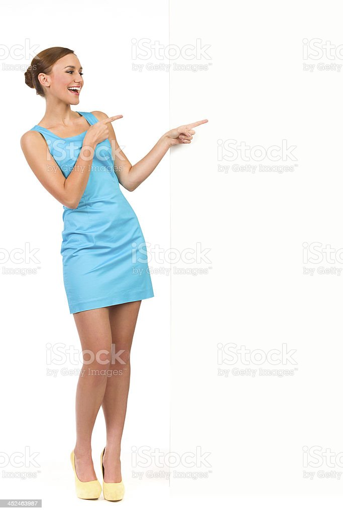 Happy Young Black Woman Pointing Away On Gray Wall And