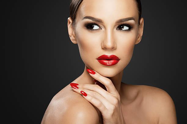 Beautiful woman portrait, beauty on dark background, red nails stock photo