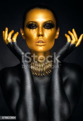 istock Beautiful woman portrait in gold and black colors 576922854