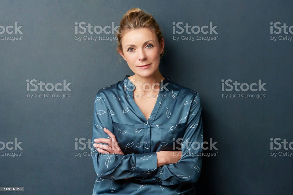Beautiful woman portrait Studio shot of a smiling attractive middle aged woman standing with arms crossed at dark background. 40-49 Years Stock Photo