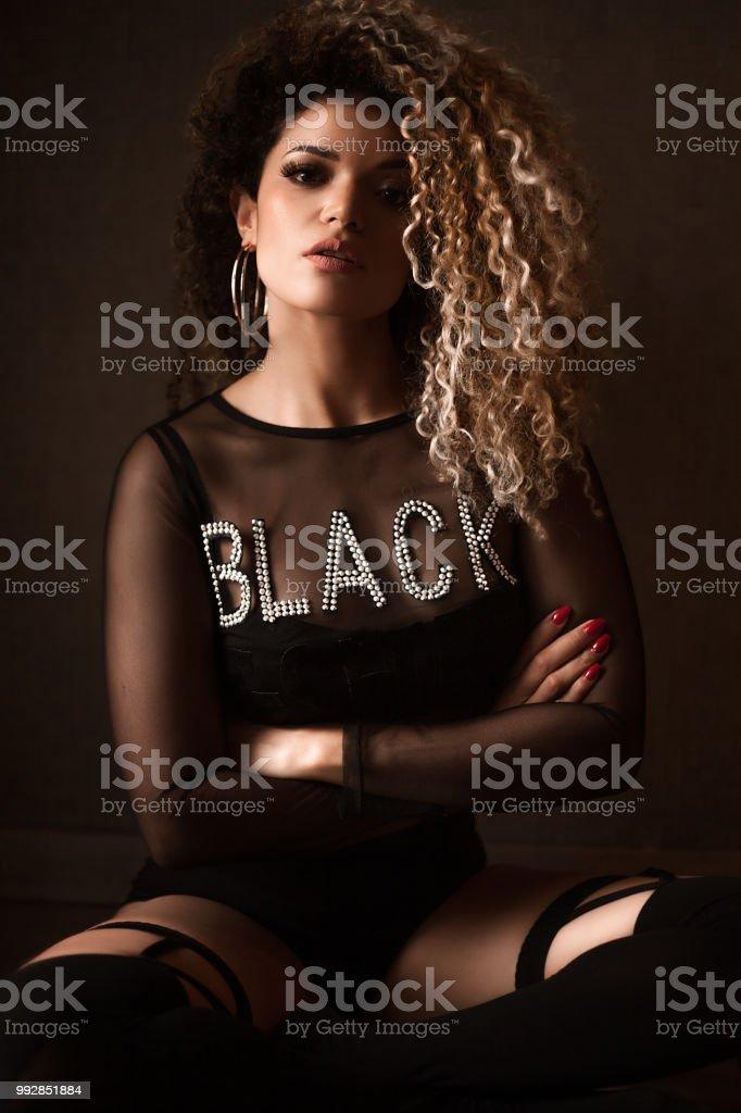 1beed179f Retrato de mulher bonita com cabelo lindo sentado com os braços cruzados e  olhando foto royalty