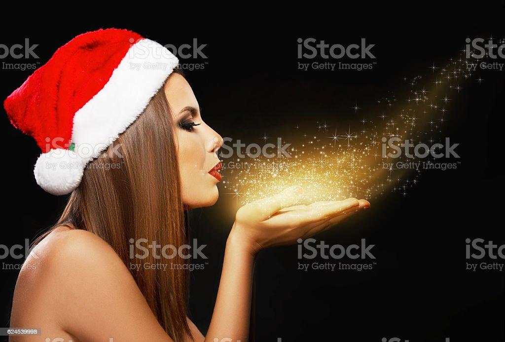 Beautiful woman portrait with Santa's hat, blowing golden dust stock photo