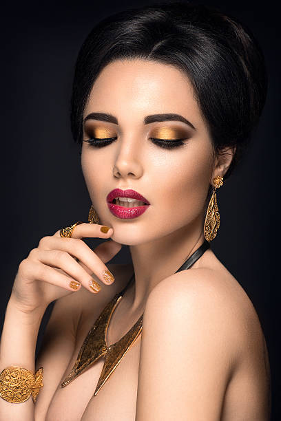 beautiful woman portrait. young lady posing with gold jewelry - goldenes augen make up stock-fotos und bilder