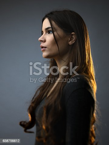 Beautiful woman posing against against grey background. Beautiful female with long brown hair is standing. She is wearing casual clothes. Vertical studio photography from a DSLR camera. Sharp focus on eyes.