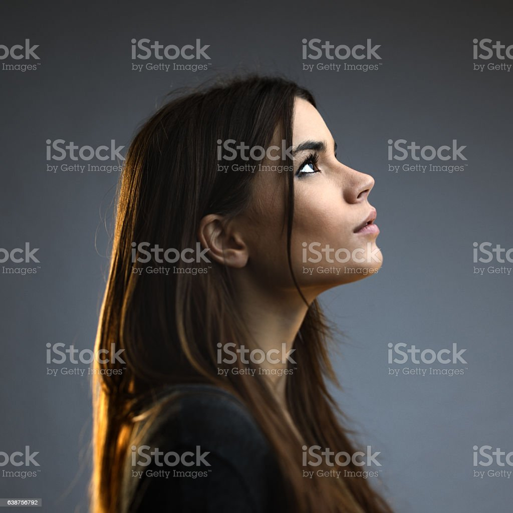 Beautiful woman posing against dark background stock photo