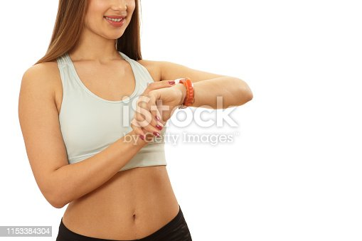 Cropped shot of an athletic woman in sports top smiling using her smart watch setting the timer before training. Sexy sportswoman with toned shapely body using sports watch for workout