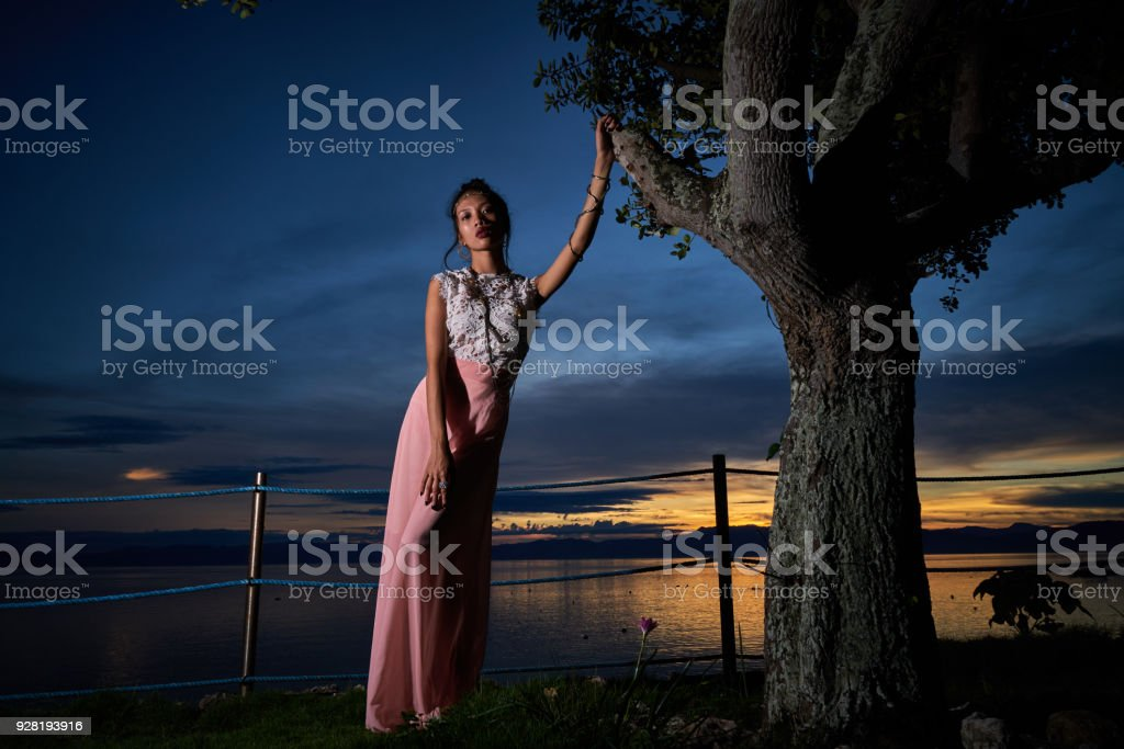 Mulher bonita posando - mão no galho de árvore - foto de acervo