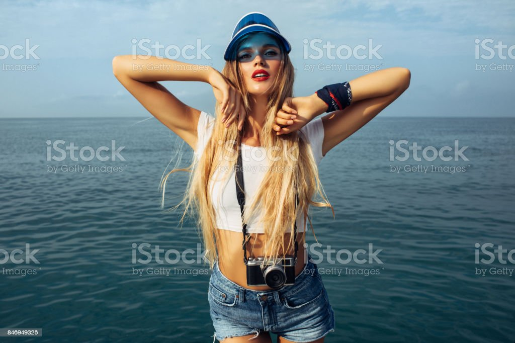 Beautiful woman posing on sea background in blue shorts stock photo